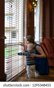 Mother with baby son look through blinds.