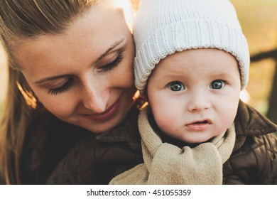 Mother with baby son on knitted hat and scarf