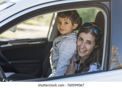 Mother and baby son posing in portrait image inside her car and looking at camera while smiling
