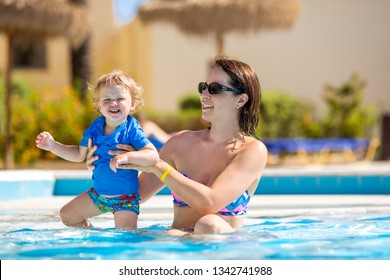 Mother and baby in swimming pool. Parent and child swim in a tropical resort. Summer outdoor activity for family with kids. Vacation and traveling with young children