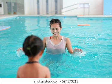 Mother with baby in swimming pool training