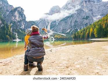 Mother and baby taking photo while on lake braies in south tyrol, italy. rear view