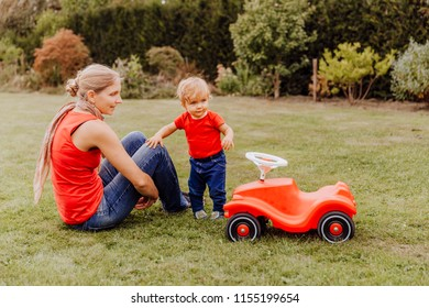 Mother and baby with toy car in garden – Kempen, Germany