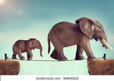 mother and baby toy elephants walking on a tightrope subtle vintage filter and lens flare
