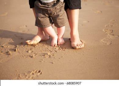 Mother and baby walking on beach sand