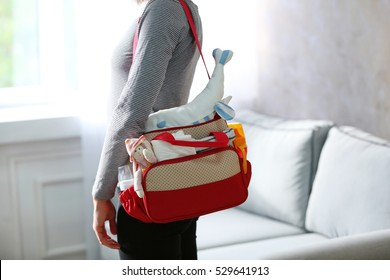 Mother with bag for baby at home