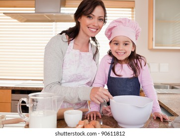 Mother baking with her daughter in a kitchen