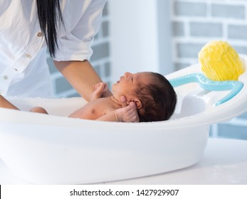 Mother bath Asian boy baby newborn on the bathtub