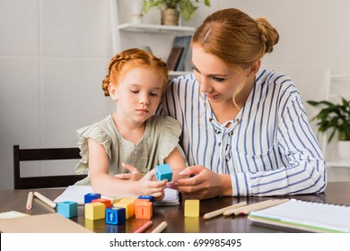 mother and beautiful concentrated daughter learning with letter cubes