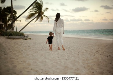 Mother and beby girl walking on tropical beach
