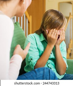 Mother berating teenager son in living room at home