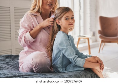 Mother is the best hairdresser. Beautiful young mother brushing her daughters hair while sitting on the bed at home