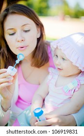 mother blowing soup bubbles - her daughter looking with smiling