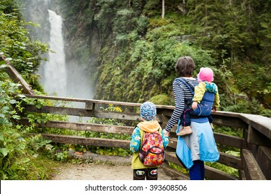 mother with boy and girl in baby carrier watching waterfall on hike in the austrian mountains near krimm