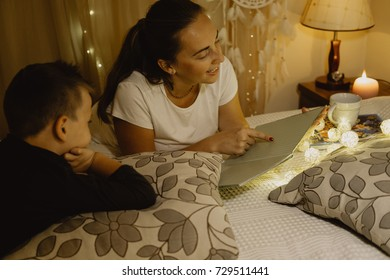 Mother and boy reading a book in bed before going to sleep