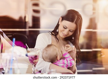 Mother breast feeding her little daughter in a cafe