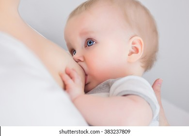 Mother breast feeding and hugging her baby.Young mother feeding breast her babyboy at home in white room. Mom  breastfeeding her child whith breast milk