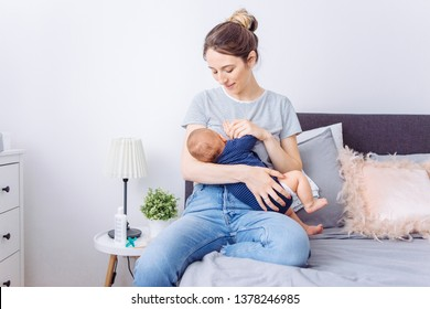 Mother breastfeeding baby son in bedroom, they enjoy in this moment together