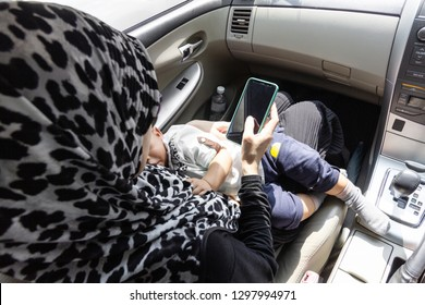 Mother breastfeeding child in a car, public breastfeeding concept.