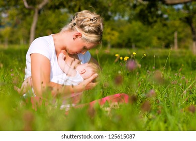 Mother breastfeeding her baby on a great sunny day in a meadow with lots of green grass and wild flowers