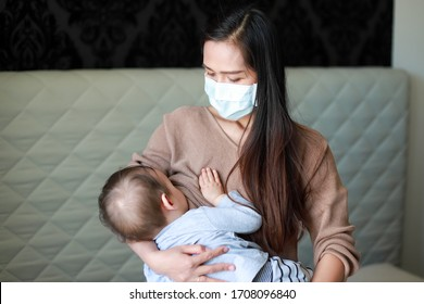 Mother breastfeeding her newborn baby in her arms while wearing medical face mask during coronavirus,Covid-19 outbreak pandemic.asian mommy with child sickness or allergy quarantine stay at home.