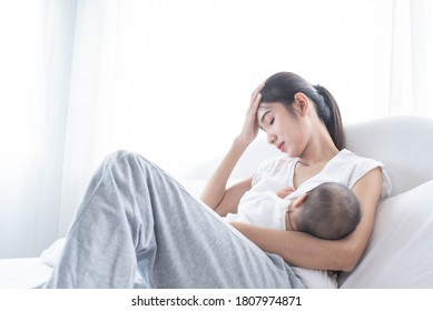 Mother breastfeeding her newborn baby beside window. Milk from mom's breast is a natural medicine for children. Young woman feeding baby. The mother was exhausted from raising children.