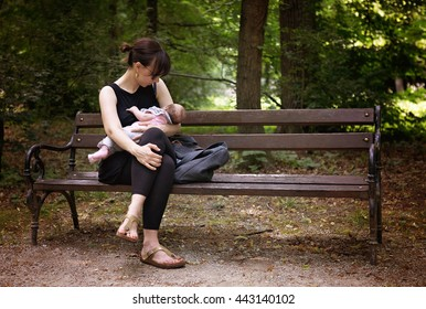 Mother breastfeeding her newborn baby girl in the park on demand, sitting on the bench under the trees, instagram style effect applied