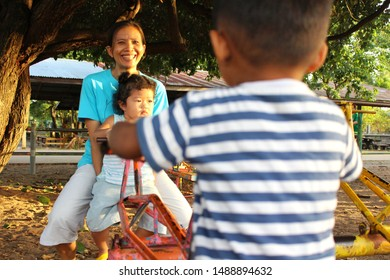Mother brought her daughter and son to play in the playground. In the evening, golden yellow sunshine, blurry photography