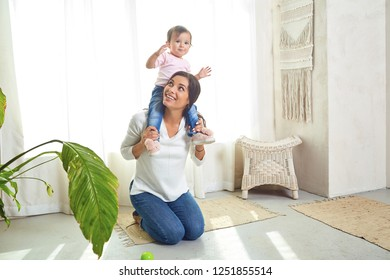 Mother brunette plays with the child at home.