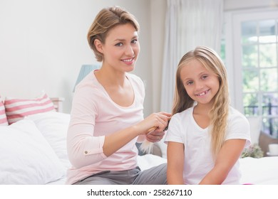 Mother brushing her daughters hair at home in the bedroom