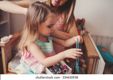 mother brushing toddler daughter's hair at home, casual lifestyle