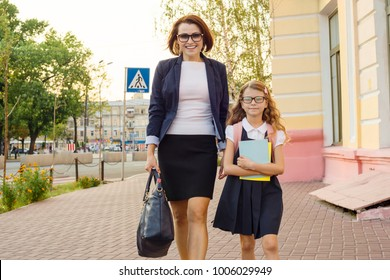 Mother businesswoman takes the child to school. Urban style background