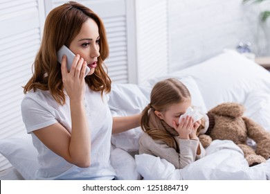 mother calling doctor by smartphone, sick daughter blowing nose in bed
