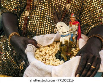 Mother of Candomble saint holds a basket with popcorn and the image of Saint George (Ogum) in front of the Church