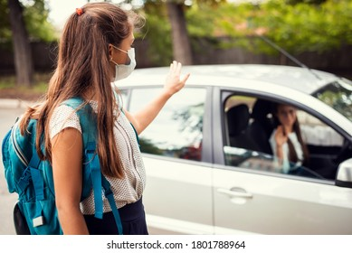 Mother in car, dropping off her daughter to the school and wishing her a good day. Back to school, motherhood concept.