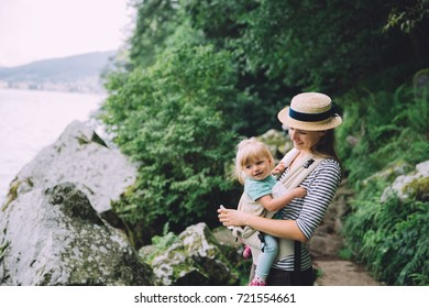 Mother caring her baby in baby carrier near the lake in the mountains in France, Alsace, Gerardmer.