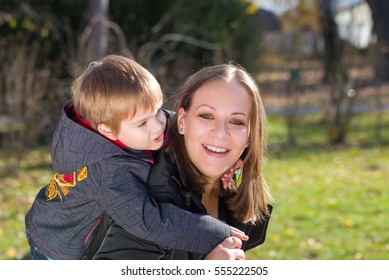 mother  carries her son on her back in park outdoor