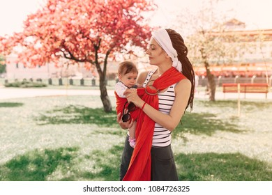 Mother carry a infant baby in wrap sling in park. Springtime. Concept of natural parenting Happy family spring concept