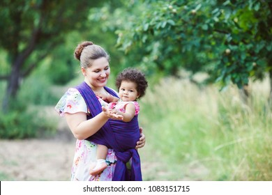 Mother carry a one year old mixed-race baby in wrap sling in park. Springtime. Concept of green parenting