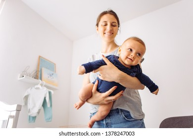 Mother carrying baby son in bedroom, they playing flying airplane