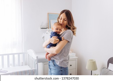 Mother carrying baby son in bedroom, they share moment of love