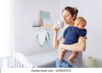 Mother carrying baby son in bedroom and drinking coffee, they share moment of love