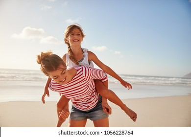 Mother Carrying Daughter On Shoulders On Beach Vacation