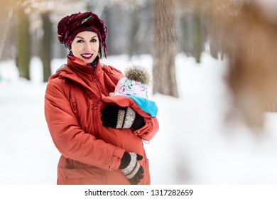 Mother carrying her baby girl wears red jacket and sling. Outdoor family fun time in winter,