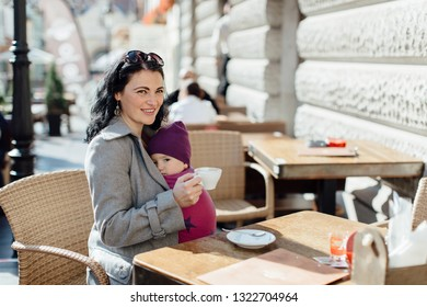 Mother carrying her child in woven wrap. Young babywearing woman enjoying her cup of coffee in cafe on sunny day.
