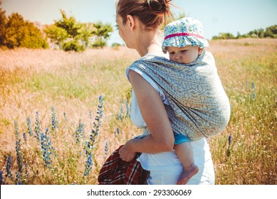 Mother carrying her little child in a baby sling