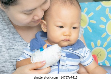 Mother carrying and hug her baby sick in hospital,saline intravenous on hand baby,children illness.A little baby attaching intravenous tube to patient's hand.Kid hand with saline intravenous, admitted