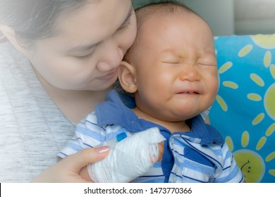 Mother carrying and hug her baby sick in hospital,saline intravenous on hand baby,children illness.A little baby attaching intravenous tube to patient's hand.Kid hand with saline intravenous, admit