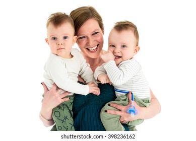 Mother is carrying identical twins boys and smiling. Happy family with twins and happy mother.