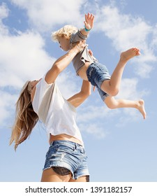 Mother carrying and playing to fly with boy son against sunny blue sky space, outdoors. Family vacation fun activities and games, leisure recreation lifestyle, bonding healthy holiday summer living.